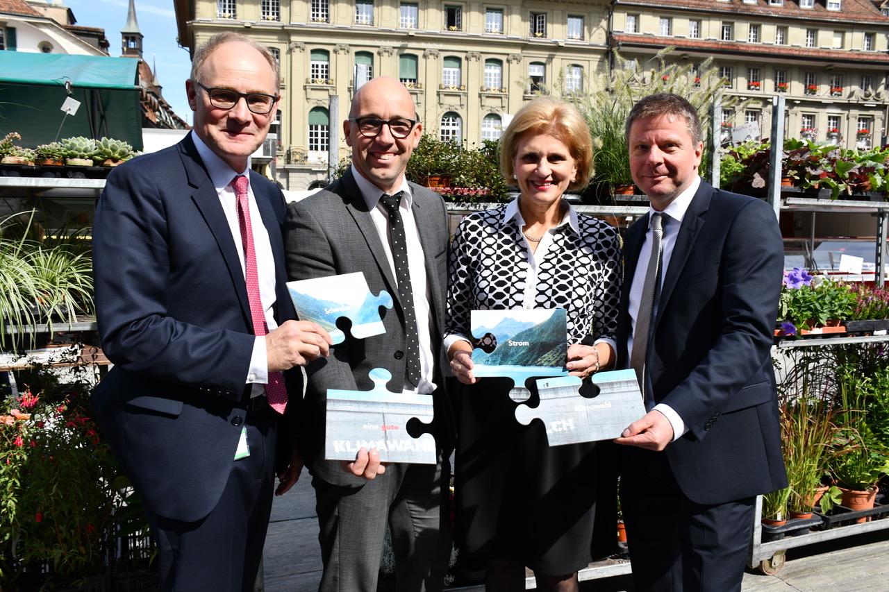 Symbolisch für den offenen Dialog strecken diese vier Parlamentarier die Puzzleteile «Schweizer Strom ist eine gute Klimawahl» zusammen. Von links nach rechts: Hans-Jörg Knecht, Stefan Müller-Altermatt, Doris Fiala, Martin Bäumle.
